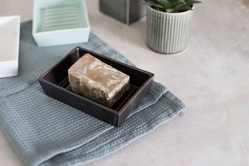 13 Ideas For Creating A More Manly, Masculine Bathroom // A dark ceramic or concrete soap dish will keep the soaps off the counter, helping to keep it clean and clutter free.