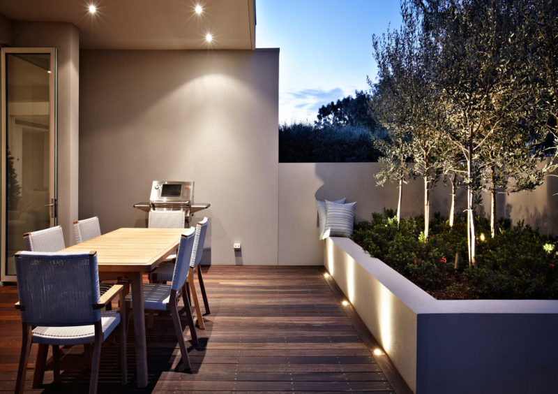 17 Inspiring Examples Where Exterior Uplighting Has Been Used To Show Off A House // Lights next to and inside of the large built-in planter add brightness and drama to the patio.