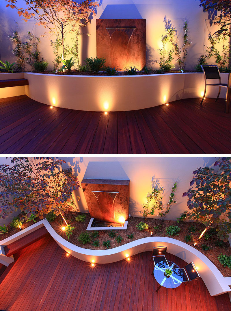 17 Inspiring Examples Where Exterior Uplighting Has Been Used To Show Off A House // Recessed lighting on this curved patio and inside the planters brighten the outdoor space and create a dramatic effect with the shadows behind the plants and metal installation.
