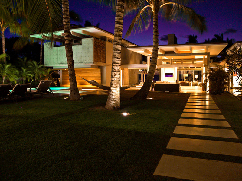 17 Inspiring Examples Where Exterior Uplighting Has Been Used To Show Off A House // Uplighting highlights specific features of this home, such as the palm trees and roof-line.