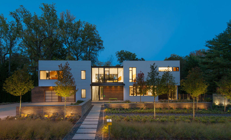 17 Inspiring Examples Where Exterior Uplighting Has Been Used To Show Off A House // The lights used at the front of this house brighten the entrance and illuminate the plants in the front yard.