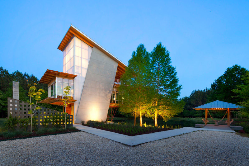 17 Inspiring Examples Where Exterior Uplighting Has Been Used To Show Off A House // Uplighting illuminates the bottom of the large trees and the entry way of this home.