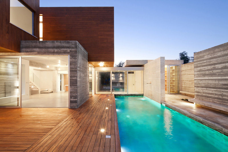 17 Inspiring Examples Where Exterior Uplighting Has Been Used To Show Off A House // Lights built into the pool deck of this house brighten the area surrounding the pool adding an element of safety to the deck.