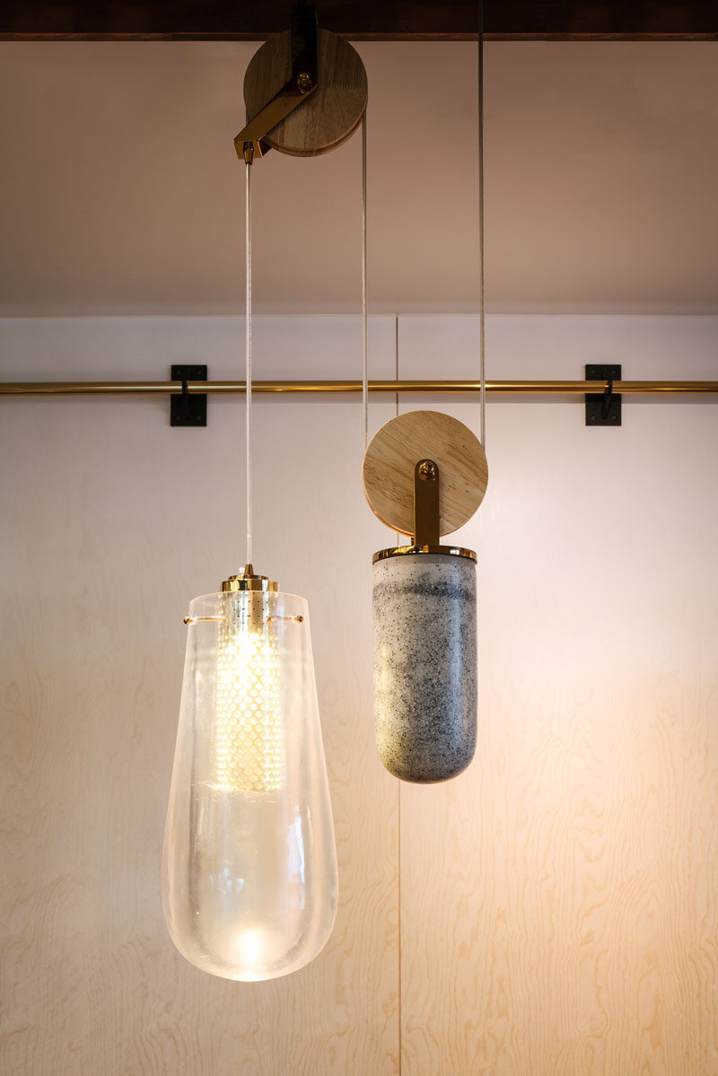 The custom-designed pendant lights that are on a pulley system, consist of a drop pendant light made from cast resin, a counterweight made from cast concrete, and brass details with a diffused COB LED light within.