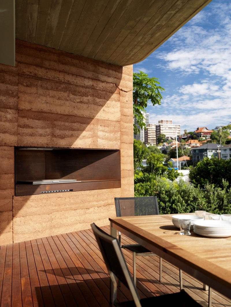 A rammed earth wall surrounds a bbq.