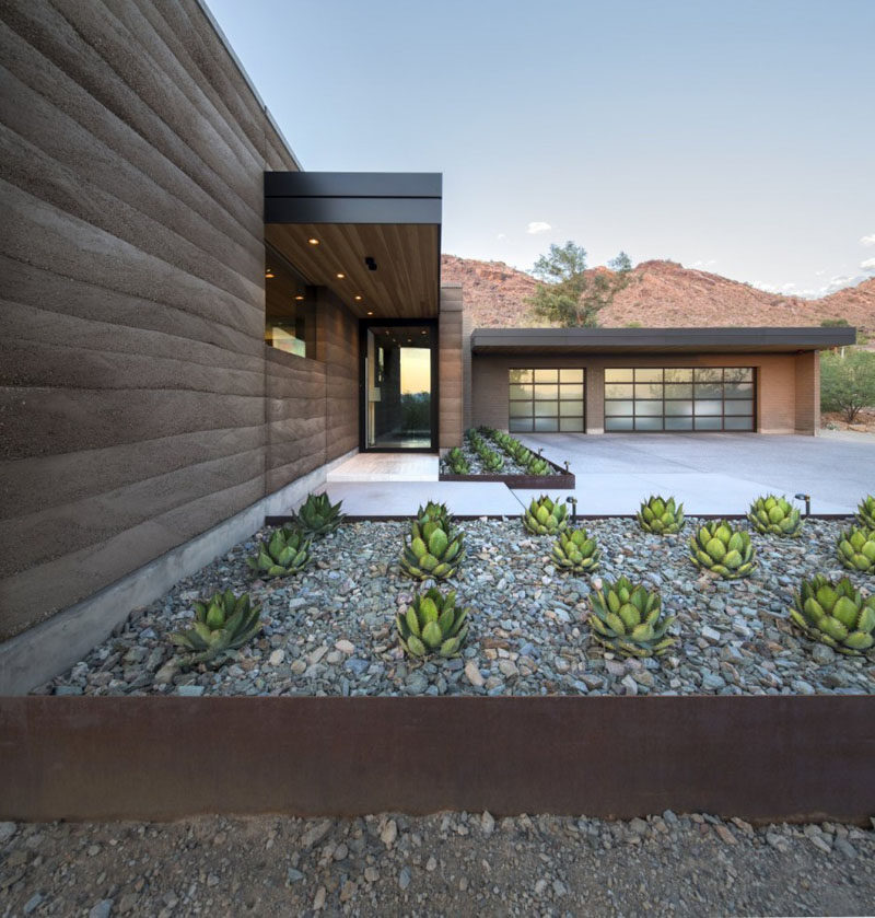 A rammed earth wall complements the planters.