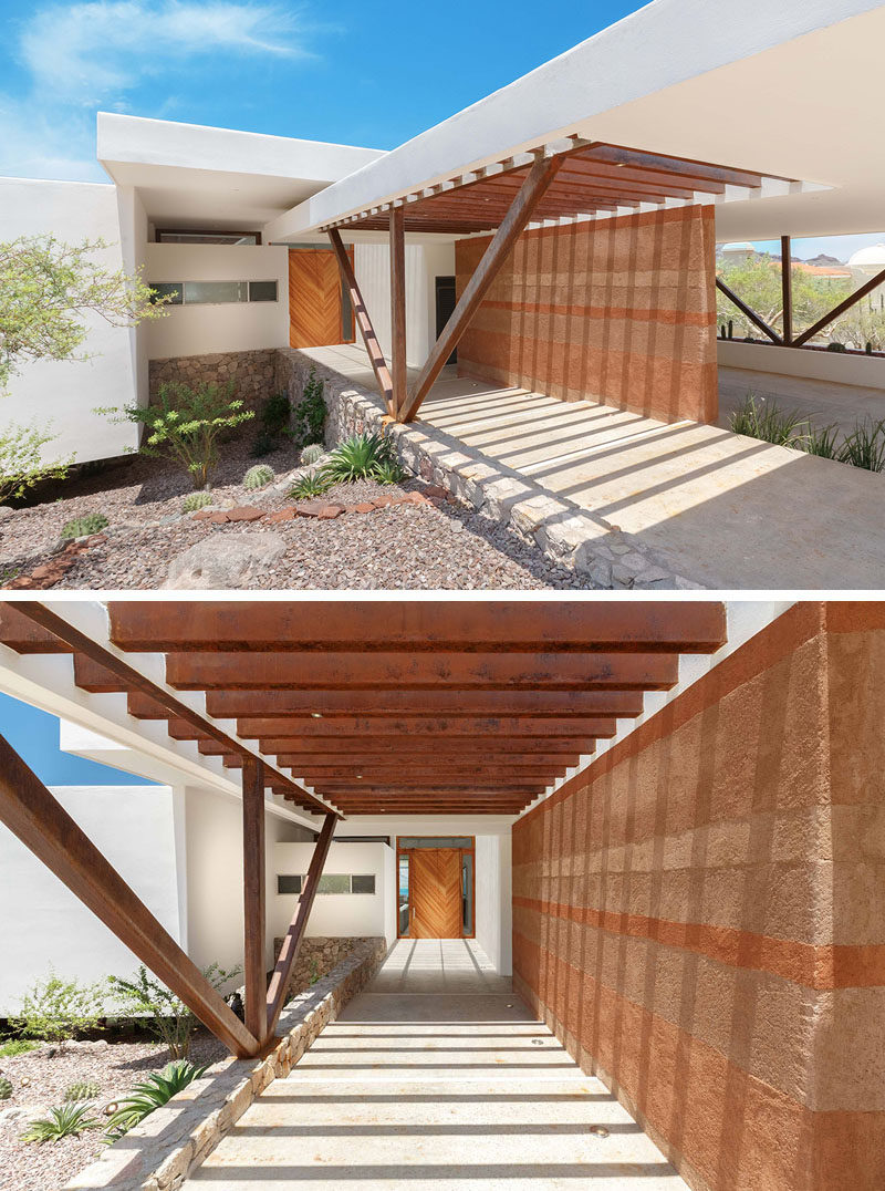 A rammed earth wall greets visitors to this modern house.