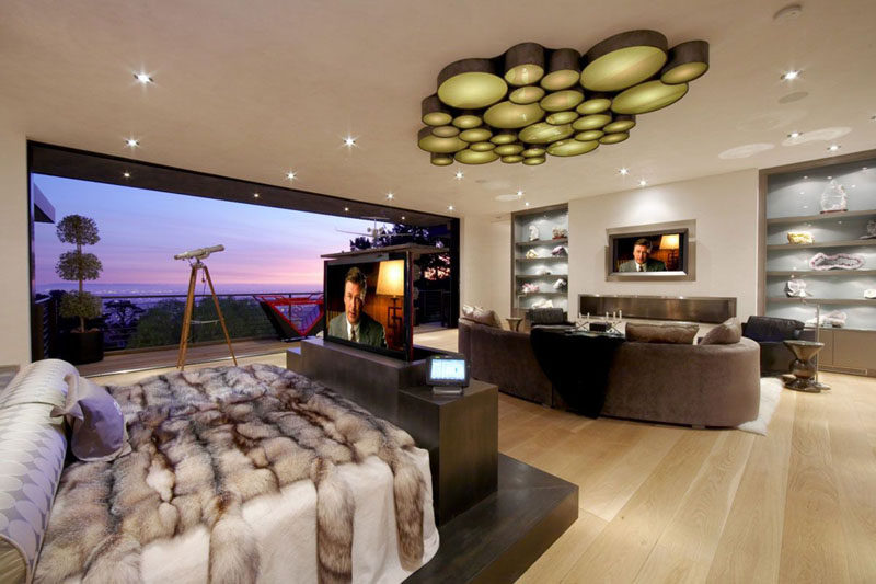 A TV built into the bed frame and  rises up when needed, while another TV is on the wall for watching shows on the couch.
