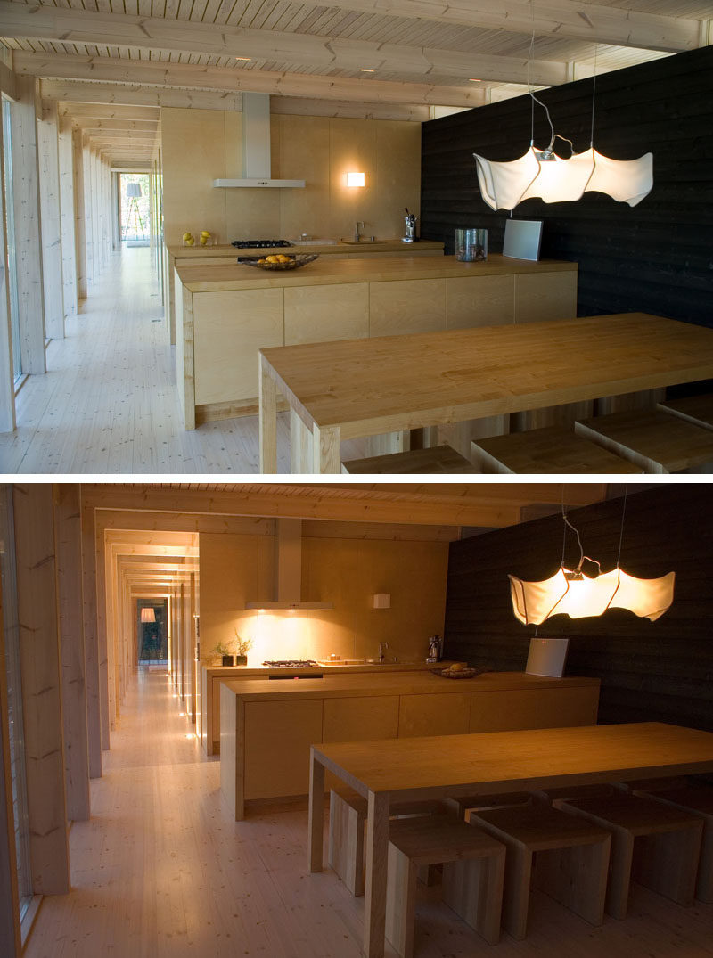 This cottage in Finland has an open dining and kitchen area. Birch plywood contrasts against the stained black wood wall on the right.