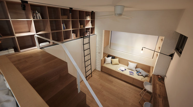 This small apartment has a bookshelf above a wardrobe, that can be reached by ladder.