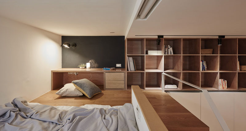 In this small apartment, there's s a small built-in desk area, and above the wardrobe, there are exposed shelves for additional storage.