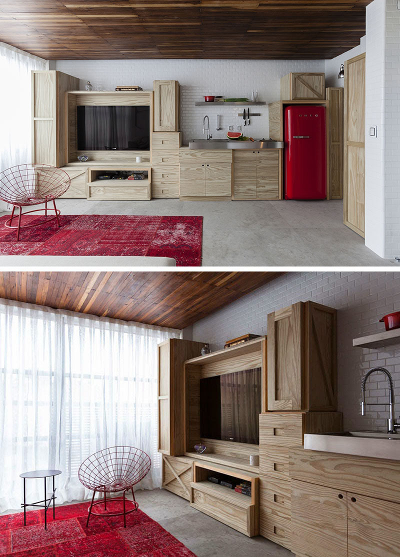 Along one wall in this small apartment is custom built cabinetry that combines the entertainment unit and the kitchen.