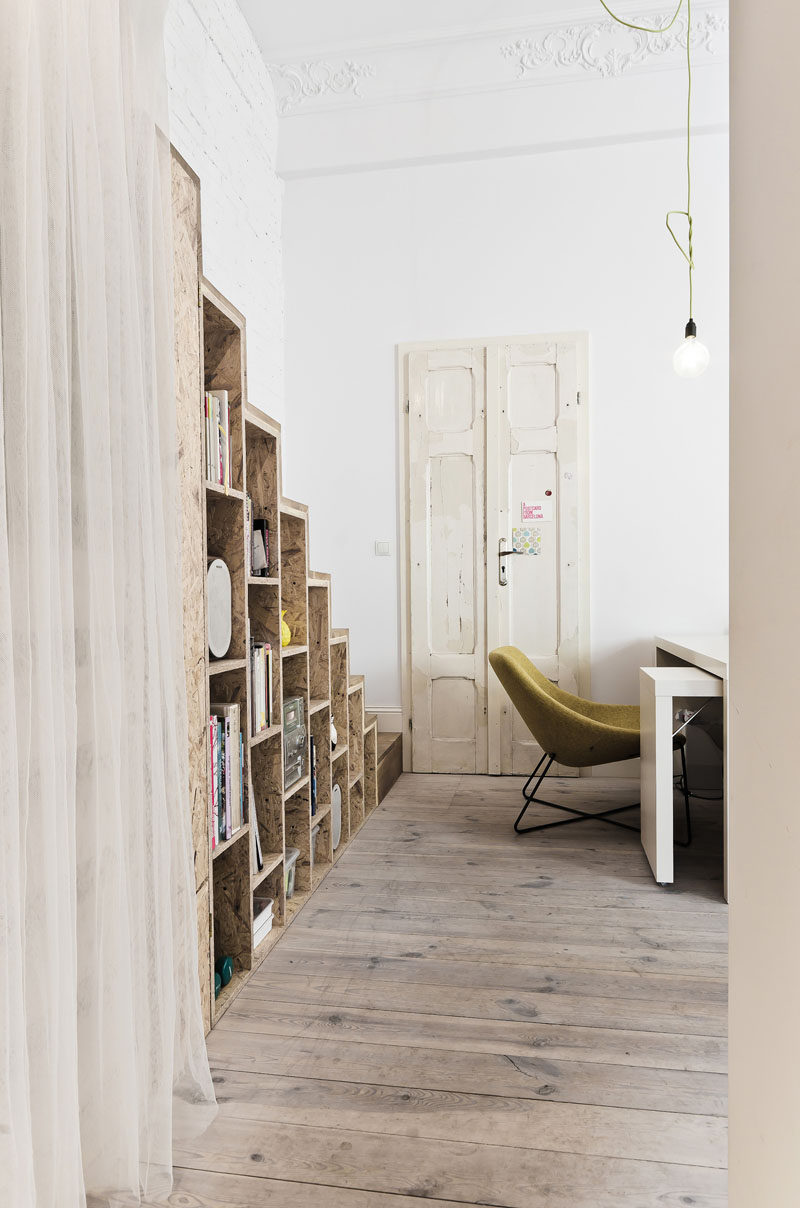 These wooden stairs in a small apartment, have an open bookshelf built into them.