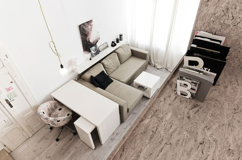 This living area in a small apartment, has a sofa for relaxing and a desk for working.