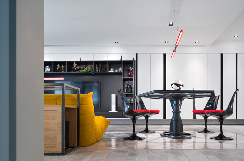 The design of the dining table in a Star Wars inspired apartment, is based on the Imperial Army TIE fighter, with a Darth Maul double-bladed lightsaber chandelier.