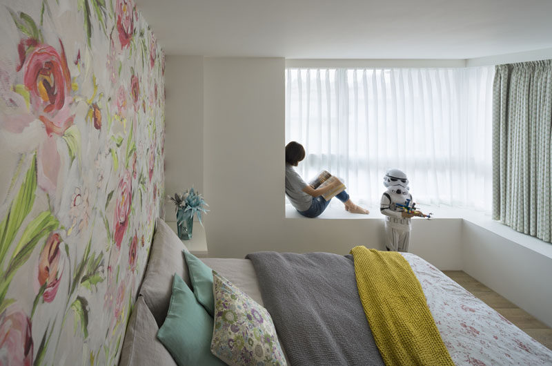 In this bedroom, the colors are a soft tone and there's a built-in bench next to the window.