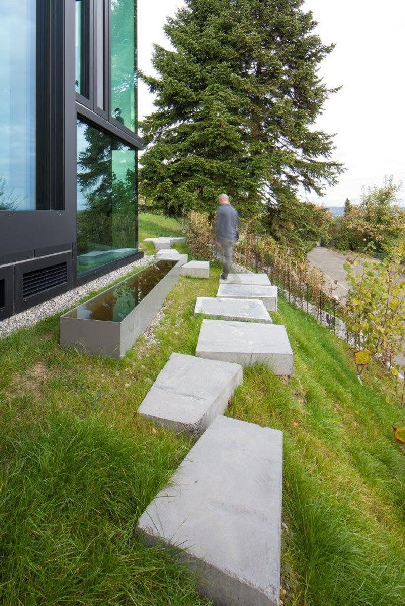 10 Ideas for Stepping Stones in Your Garden // Large concrete stepping stones line the side of this sloping yard making for an easy path around the house.