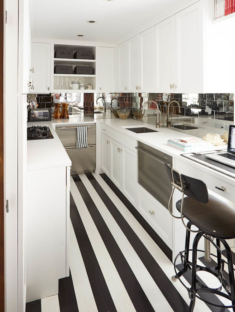 The black and white stripes in this tiny kitchen elongate it and create the illusion that the kitchen is bigger than it actually is