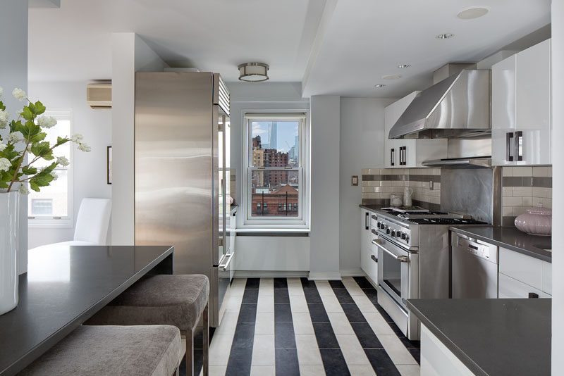 7 Examples Of Striped Floors In Contemporary Homes // Shiny stainless steel coupled with the worn in striped tile floor make this apartment feel modern yet cozy and sophisticated.