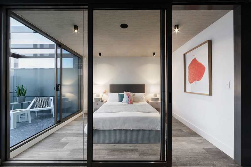 This bedroom has glass walls that allow plenty of light into the room, and there's a small private balcony to the side.