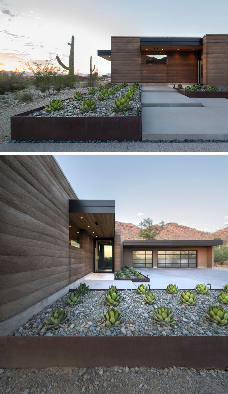 9 Ideas For Including Weathering Steel Planters In Your Garden // The rows of succulents and large rocks within these weathered steel planters help make the front of this desert house welcoming and up the house's curb appeal. #SteelGardenPlanters #WeatheredSteelPlanters #CortenSteelPlanters #Landscaping #GardenIdeas #PlanterIdeas