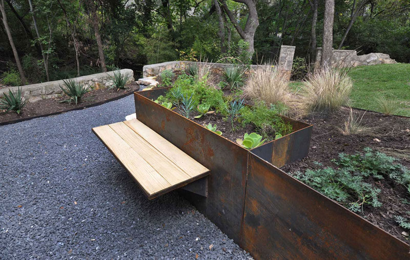 9 Ideas For Including Weathering Steel Planters In Your Garden // This planter / bench combination made from wood and weathered steel lets someone sit and enjoy the garden.  #SteelGardenPlanters #WeatheredSteelPlanters #CortenSteelPlanters #Landscaping #GardenIdeas #PlanterIdeas