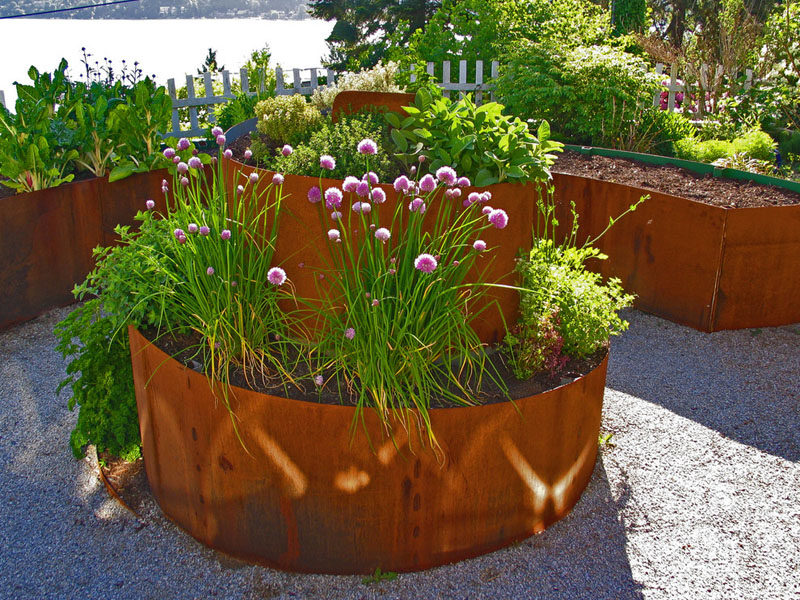 9 Ideas For Including Weathering Steel Planters In Your Garden // This weathered steel planter spirals out of the ground to add height and an artistic touch to the garden.