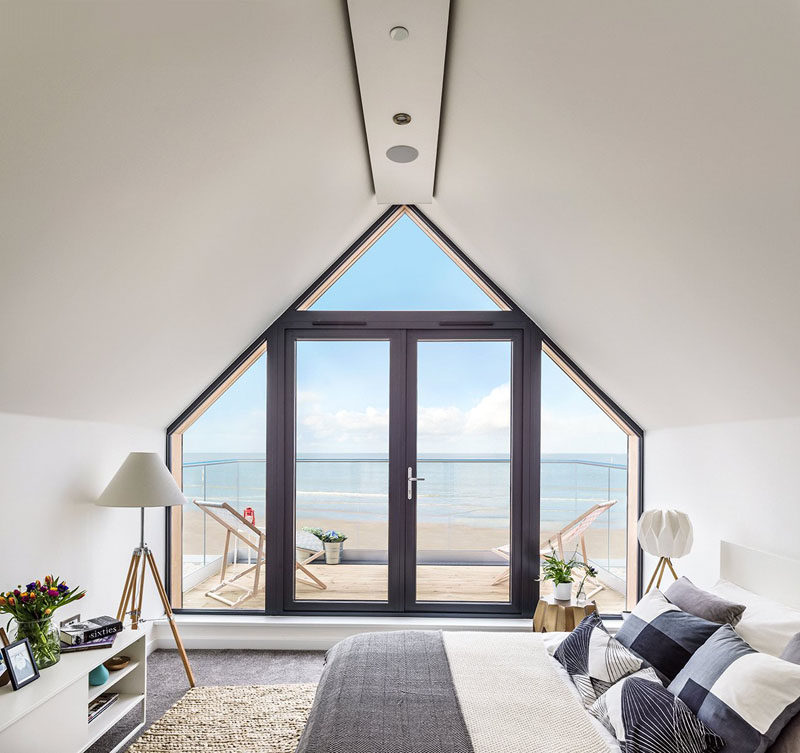 15 Awesome Examples Where Windows Follow The Roofline // This window takes up the entire wall and fits snuggly into the angles of the roof and walls to offer incredible views of the beach and ocean even from the bed.