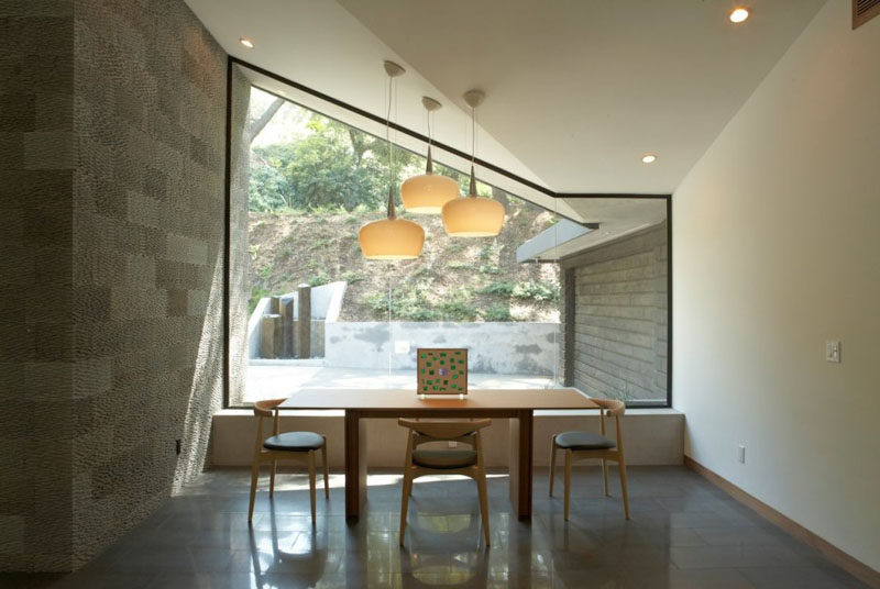 15 Awesome Examples Where Windows Follow The Roofline // The defined frame of this large window follows the angles of the ceiling and help bring in more light to the dining area of this home.