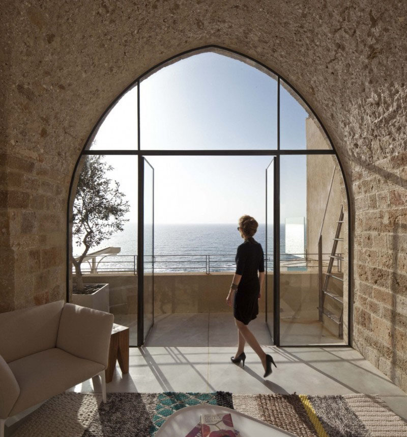 15 Awesome Examples Where Windows Follow The Roofline // This modern curved window fits perfectly into the old stone of this historic apartment building in Jaffa, Isreal and almost creates an art piece out of the sea behind it.