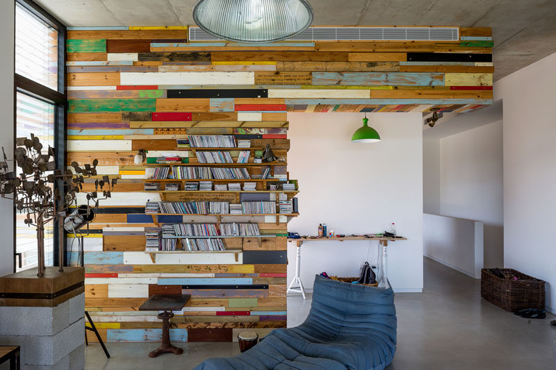 This scrap wood feature wall makes an artistic statement and hides a bookshelf.