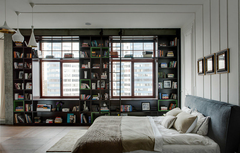 A bedroom has bookshelves that wrap around the wall, and art created from the electrical cords.