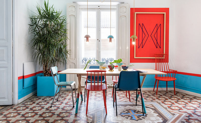 Wall Decor Inspiration - Bold Graphics Cover The Walls Of This Spanish Hostel // In this room, red artwork ties in with the red stripe around the room and red chairs.