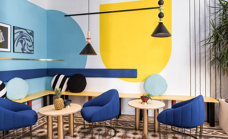 Wall Decor Inspiration - Bold Graphics Cover The Walls Of This Spanish Hostel // A pop of yellow on the wall and the seat of the bench breaks up the blue and black.