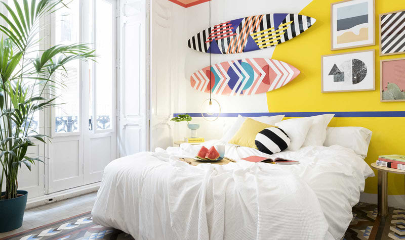 Wall Decor Inspiration - Bold Graphics Cover The Walls Of This Spanish Hostel // Fun graphics on surfboards that hang as art, add to the playfulness of this room.
