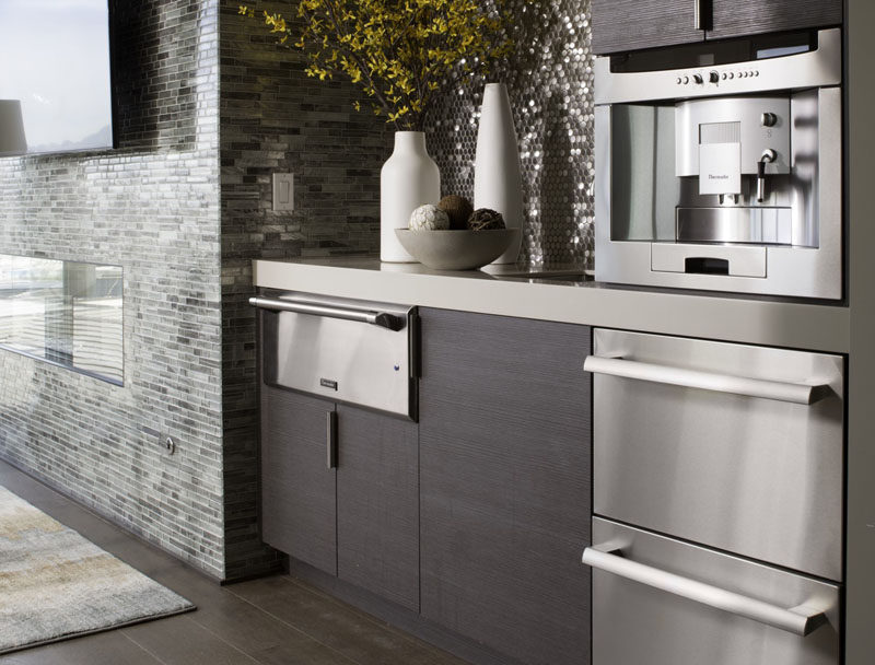 9 Examples Of Kitchens With Built-In Coffee Machines // The dark wood cupboards and the stainless steel appliances, including the built-in coffee machine, create a sleek, contemporary kitchen.