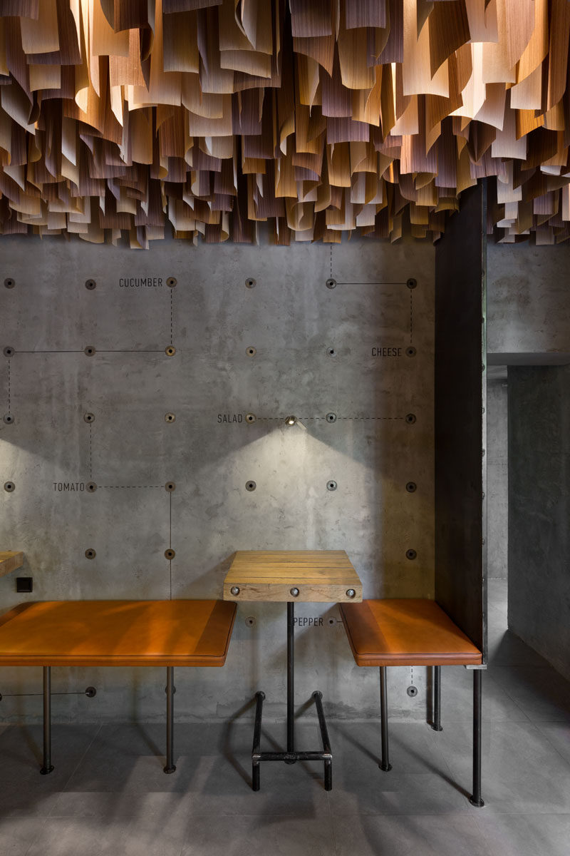 This Ukrainian burger bar has an artistic ceiling detail made from hundreds of wood veneer sheets.