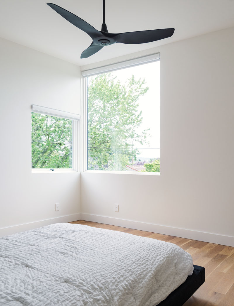 In this master bedroom, corner windows provide a view of Portland's downtown skyline and West Hills, while a black ceiling fan and bed-frame contrast the white walls.
