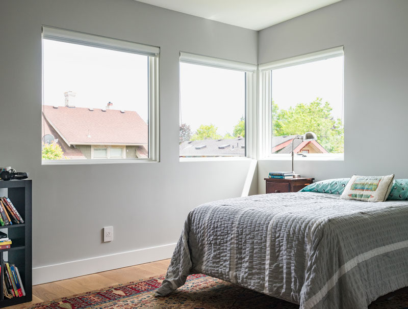 In this kid's bedroom, light gray walls are paired with custom white oak wooden flooring for a soft modern look.
