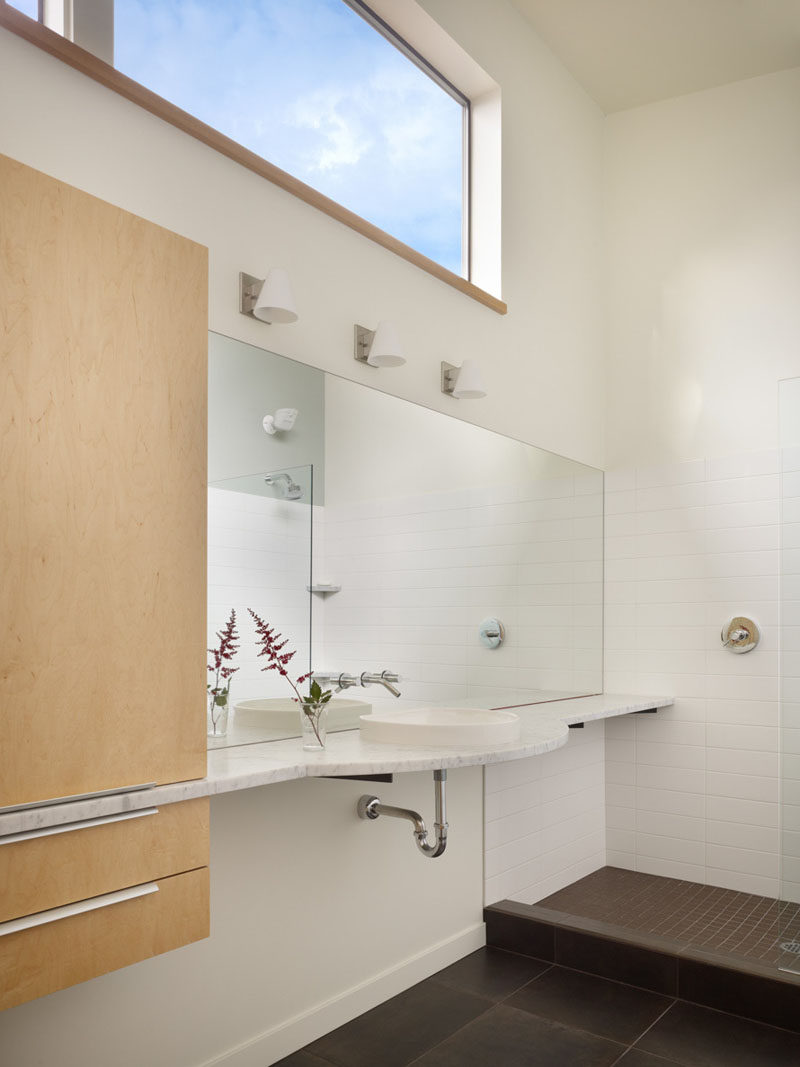 In this bathroom, the window lets in plenty of light, and the vanity runs the length of the wall, cutting through the cabinetry.