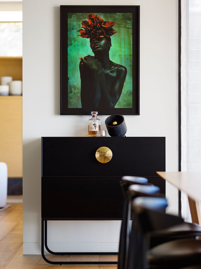 Beside the dining area, black framed artwork makes a dramatic statement.