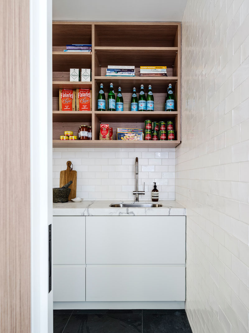 This home has a walk-in pantry room hidden behind the kitchen.