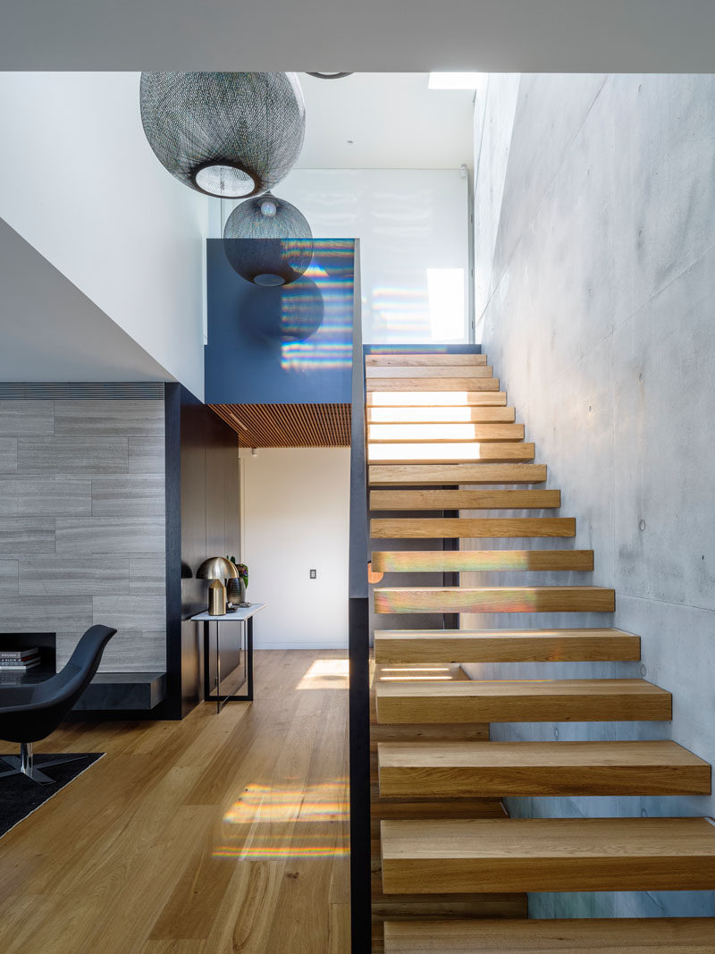 Timber clad cantilevered stairs, positioned against the off-form concrete wall, guide you to the upper level of this home.