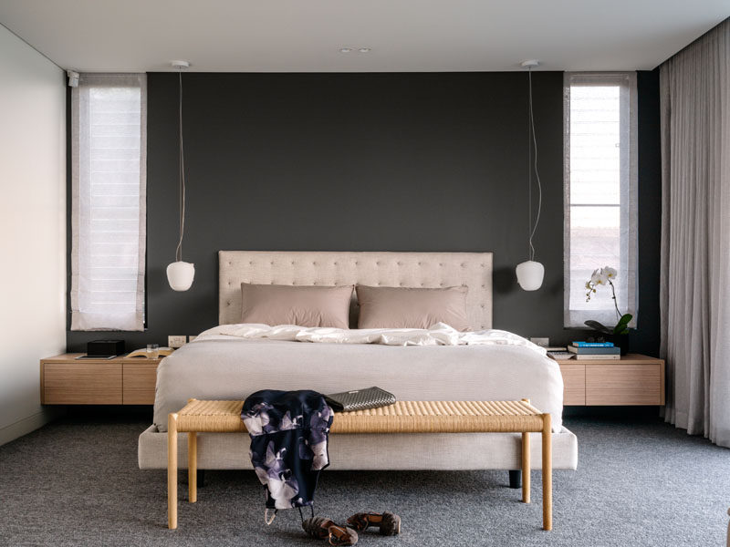 A dark feature wall contrasts the soft color palette of the bed and furniture.