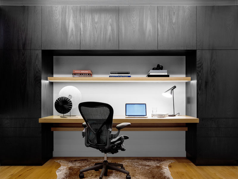 This home office is surrounded by black cabinetry, directly contrasting the wooden desk and shelf, and the white wall.