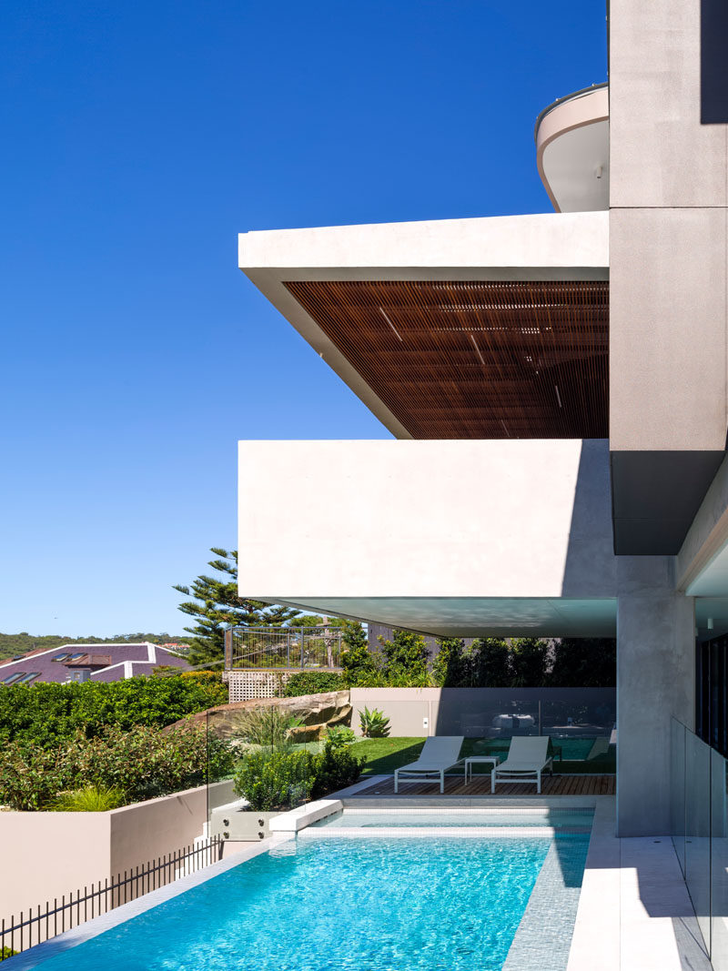 This Australian home opens up to a glass-enclosed swimming pool with another deck for lounging.