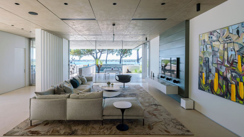 This living room has park and river views through the floor-to-ceiling windows. And outdoor dining area also shares the views.