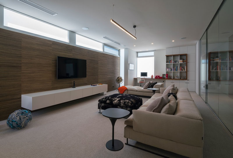 This living space with a wooden feature wall behind the tv, has a built-in desk and cabinetry at one end of the room.