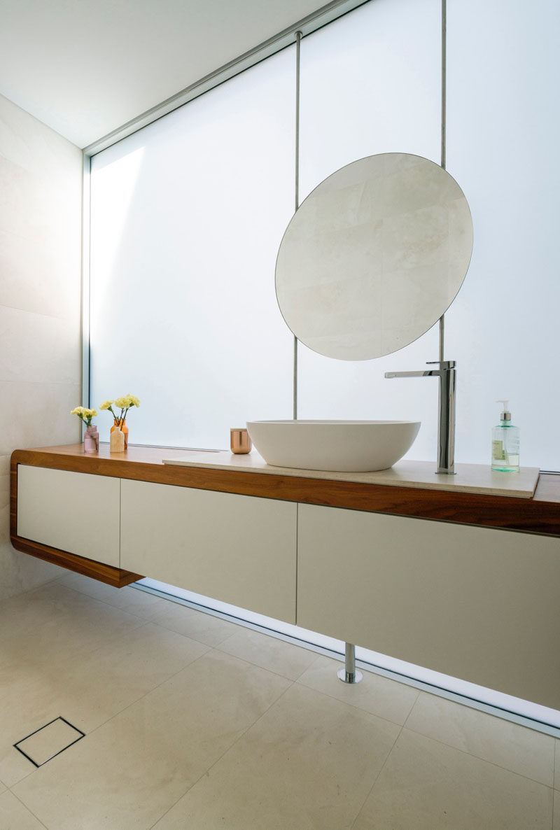 In this bathroom, a round mirror matches the curves on the oval sink, and the wood vanity breaks up the white found throughout the rest of the bathroom.