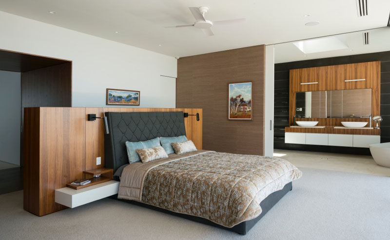 This master bedroom has sliding doors that open up to reveal an ensuite bathroom.